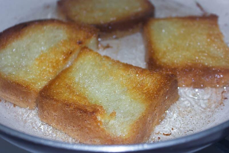 Варящ французский тост на конце сковороды вверх Зажаренный хлеб в кипя масле на лотке стоковое изображение rf