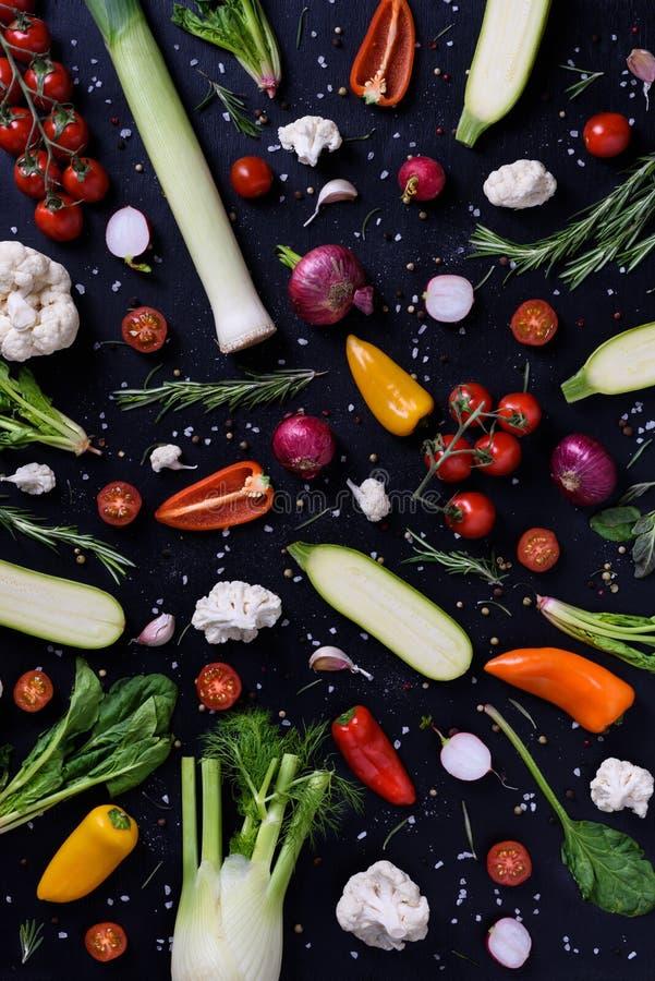 Варя и приправляя ингридиенты над чернотой Красочные овощи над деревянной предпосылкой диетпитание принципиальной схемы здоровое  стоковые фотографии rf
