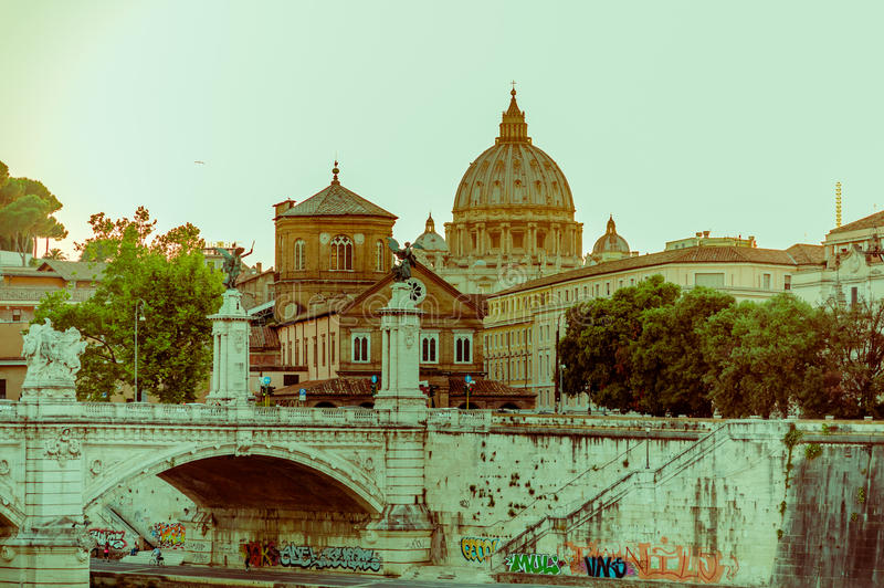 ВАТИКАН, ИТАЛИЯ - 13-ОЕ ИЮНЯ 2015: Далекий взгляд к куполу St Peter на Ватикане, graffittis под проломом и заходом солнца освещае стоковое фото rf
