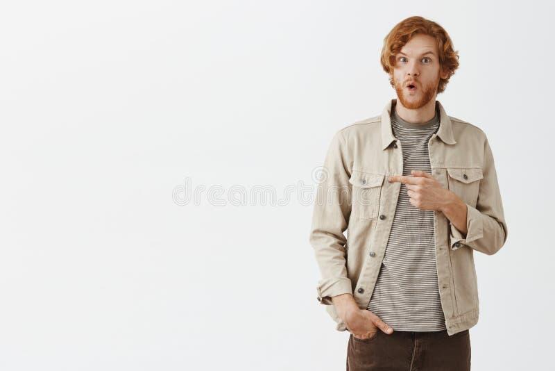 Вау интересное право предложения там портрет впечатленного и заинтригованного клиента возбужденного redhead мужского в бежевой ку стоковое фото
