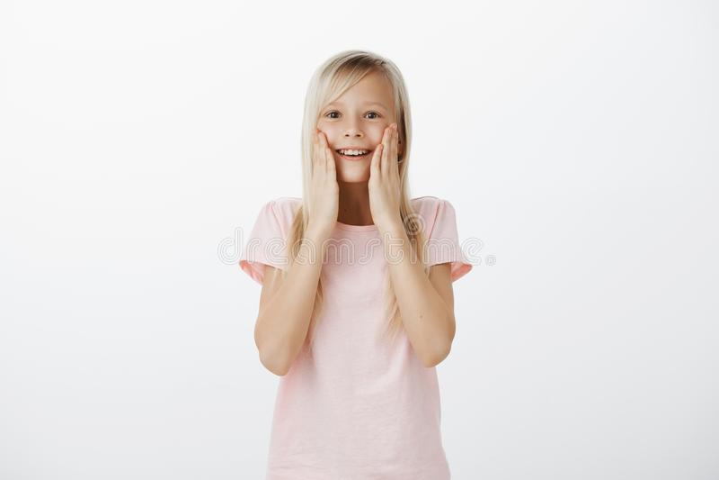 Вау, оно действительно для меня Портрет изумленной и удивленной милой маленькой девочки с светлыми волосами, держа ладони на щека стоковое фото