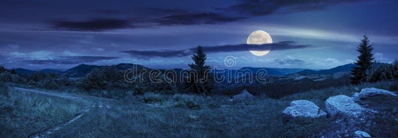 Валуны на луге горного склона в горе на ноче стоковые изображения rf
