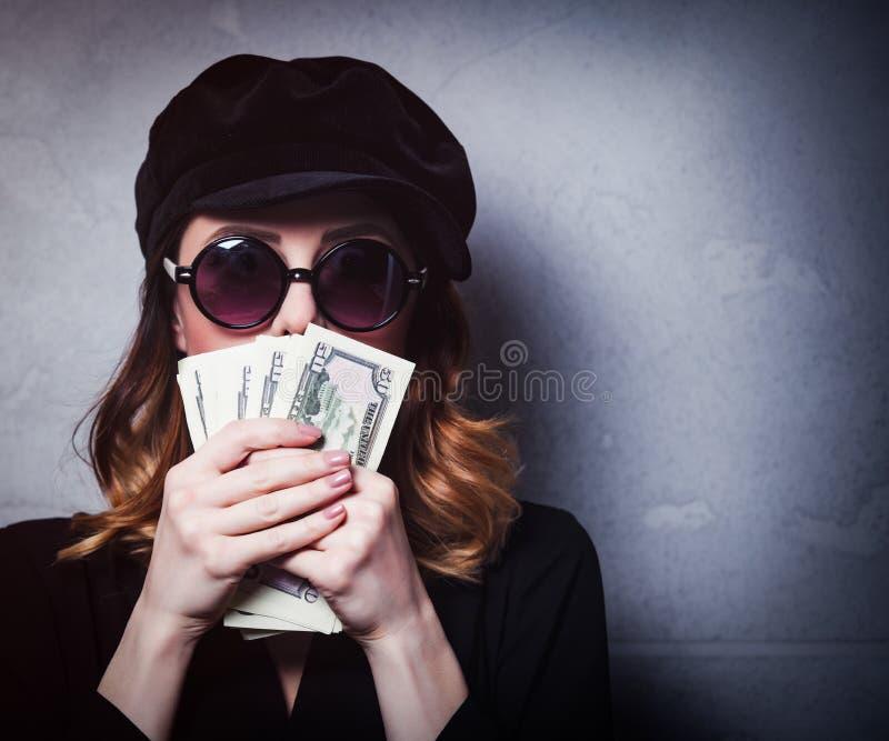 Введите девушку в моду redhead в черной шляпе и одеждах с деньгами стоковое изображение