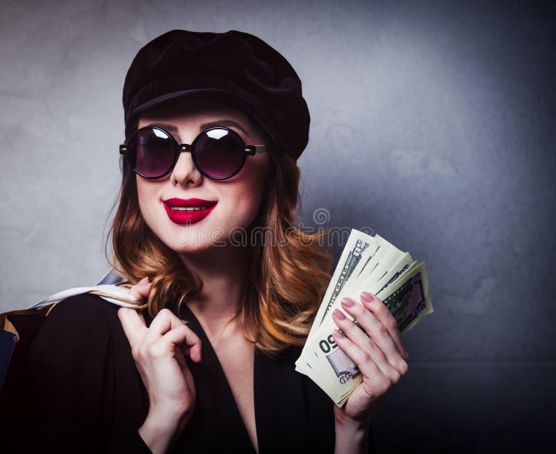 Введите девушку в моду redhead в шляпе с хозяйственными сумками и деньгами стоковые фото