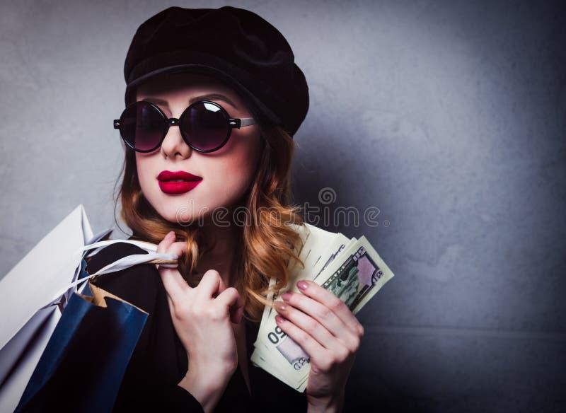 Введите девушку в моду redhead в шляпе с хозяйственными сумками и деньгами стоковые изображения