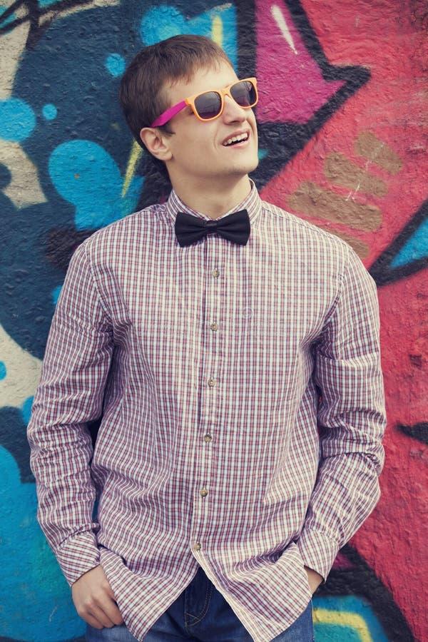 Введите предназначенное для подростков в моду в стеклах стоя близко стена граффити. стоковые фотографии rf