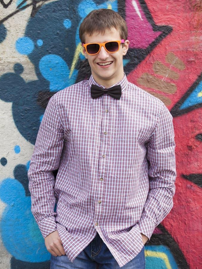 Введите предназначенное для подростков в моду в стеклах стоя близко стена граффити. стоковое фото rf