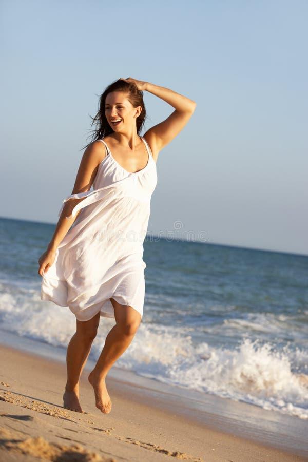 вдоль детенышей женщины лета пляжа идущих стоковые изображения