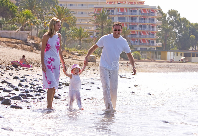 вдоль детенышей семьи пляжа здоровых солнечных гуляя стоковая фотография