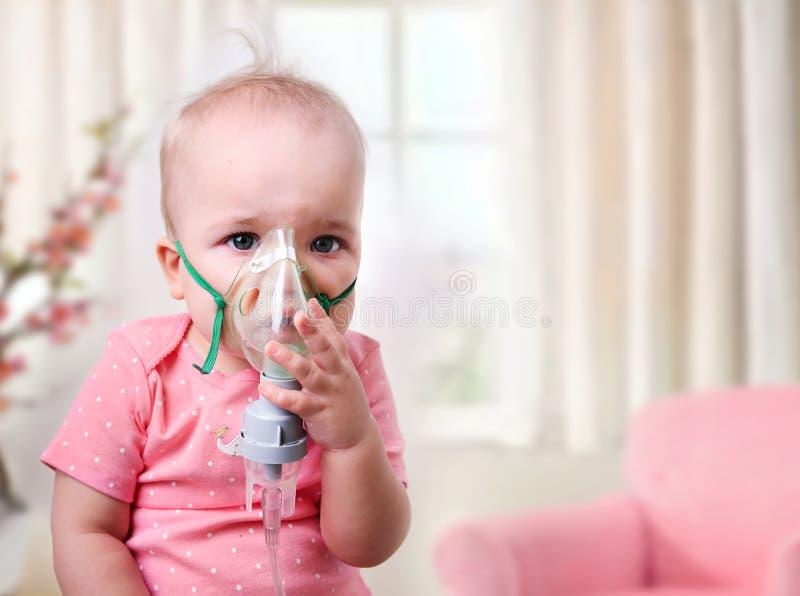 Вдыхание младенца, ребенок с маской на стороне стоковое изображение rf