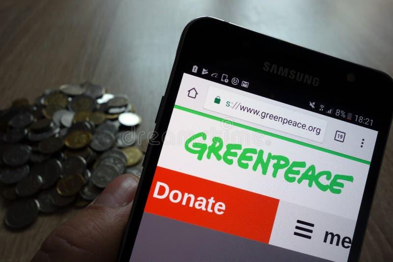 Вебсайт Гринпис показанный на смартфоне Samsung и стоге монеток стоковое фото