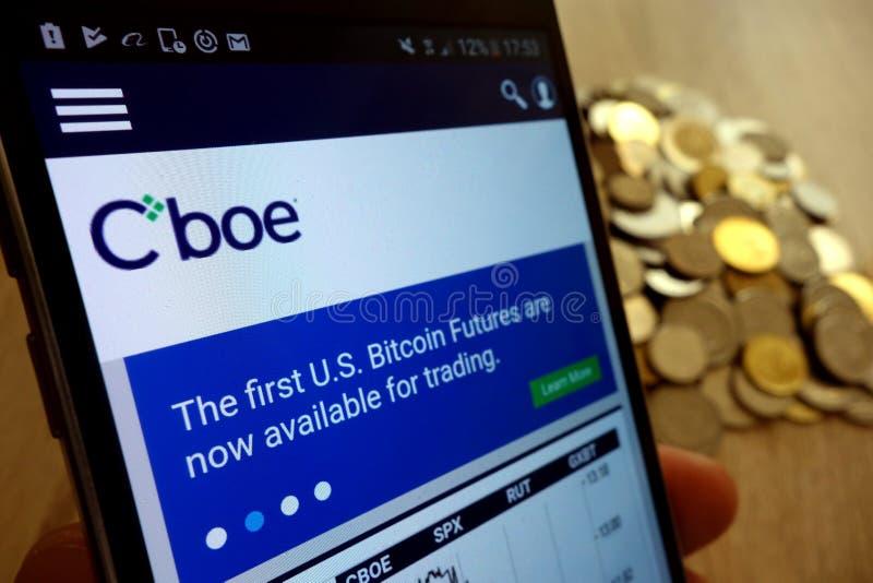 Вебсайт мировых рынков CBOE показал на смартфоне и стоге монеток стоковые фотографии rf
