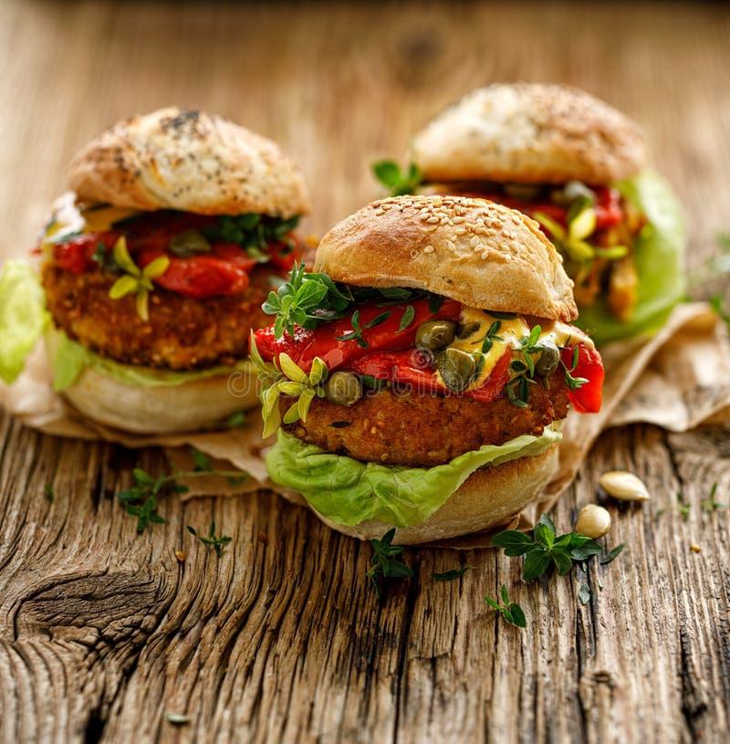Веган бургеры, Пумпкинские бургеры с добавлением жареных перцев, салата, свежих трав и капителей стоковые фотографии rf