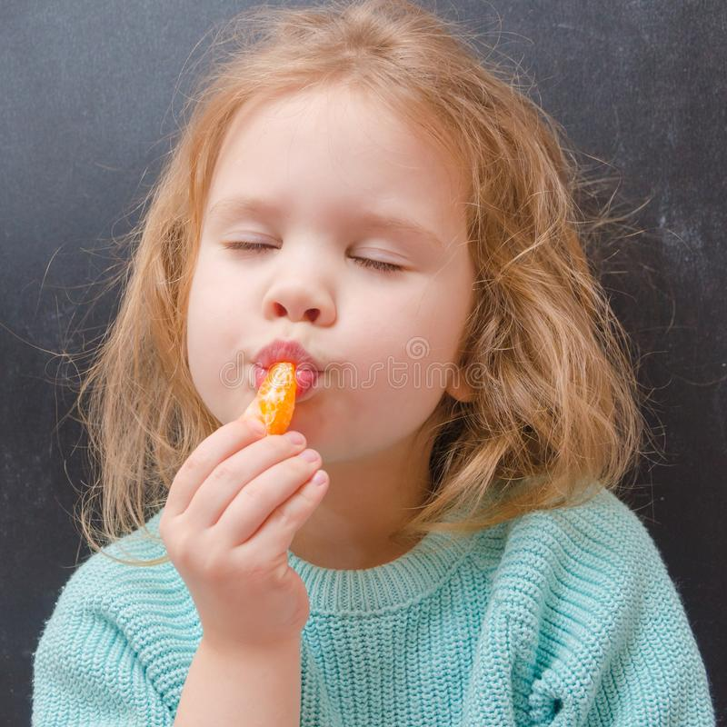 Вегетарианец ребёнка с куском мандарина стоковые изображения