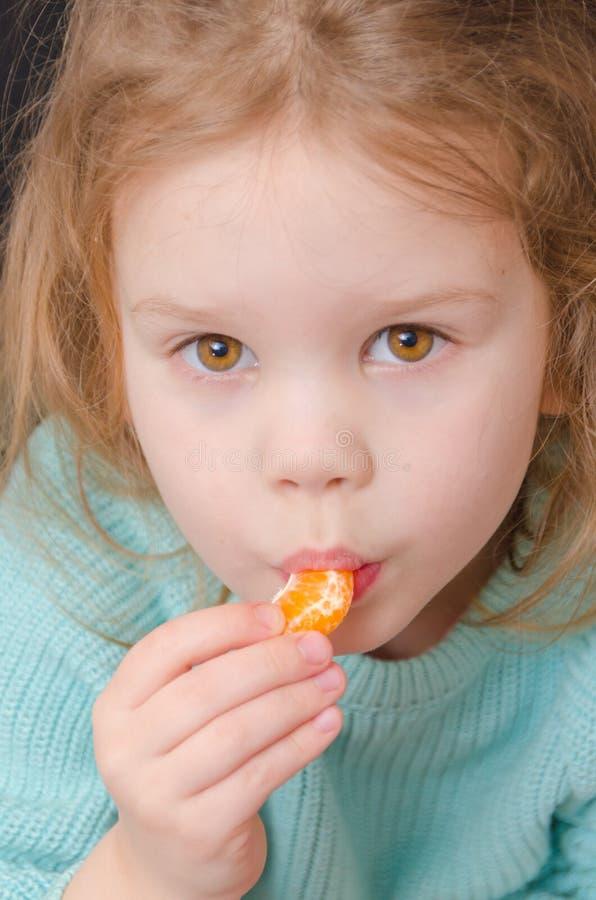 Вегетарианец ребёнка с куском мандарина стоковые фото