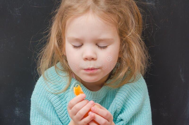 Вегетарианец ребёнка с куском мандарина стоковая фотография