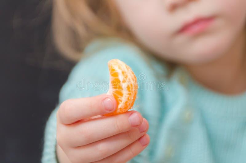 Вегетарианец ребёнка с куском мандарина стоковое изображение rf