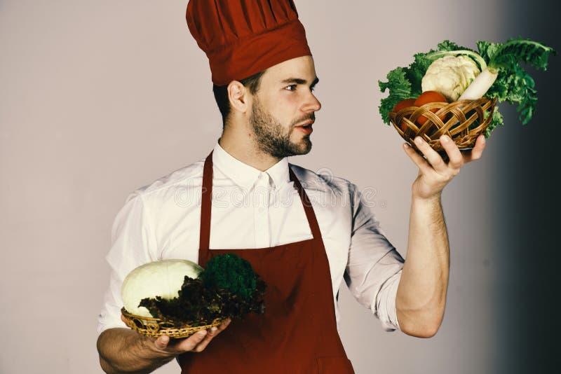 Вегетарианская принципиальная схема еды Кашевар с свежими овощами Шеф-повар с любознательной стороной держит овощи стоковые изображения rf