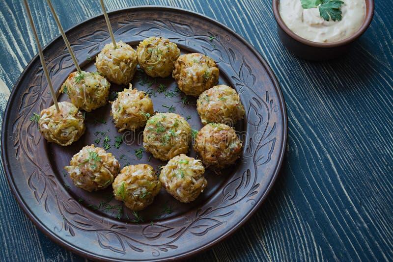Вегетарианские croquettes картошек и капусты с соусом, овощами и травами Упакованный в пергаменте Вкусный и удовлетворяющ r стоковые изображения