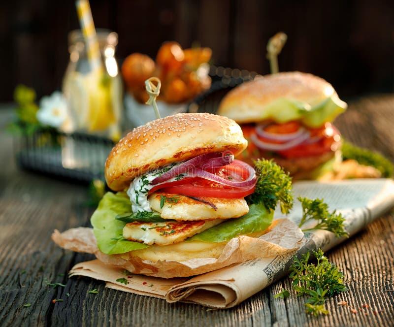 Вегетарианский бургер с зажаренным сыром halloumi, свежим салатом, томатом, огурцом и луком с дополнением соуса мяты югурта стоковые изображения