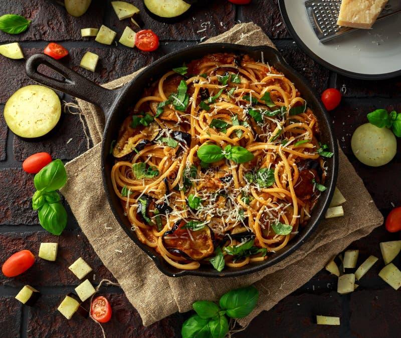 Вегетарианское итальянское alla Норма спагетти макаронных изделий с баклажаном, томатами, базиликом и сыр пармесаном в деревенско стоковые фото