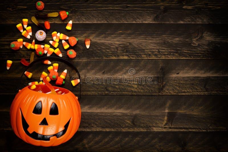 Ведерко фонарика хеллоуина Джека o с бортовой границей разливать конфету над темной древесиной стоковое фото rf