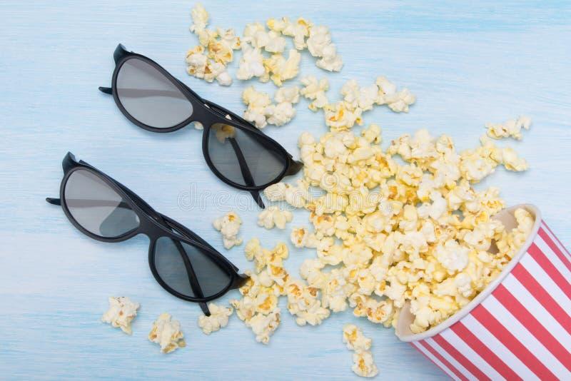 Ведро разбросанного попкорна на светлой предпосылке и паре стекел 3d стоковые фотографии rf
