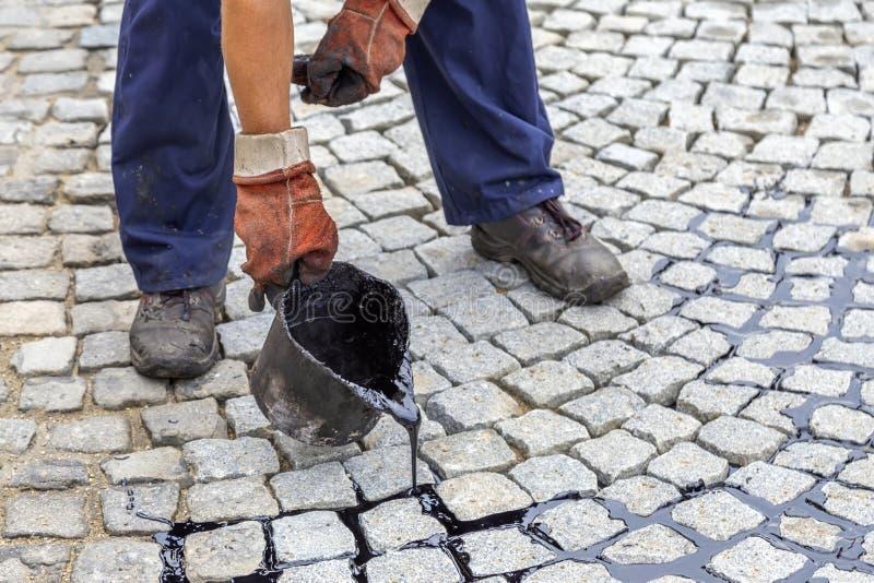 Ведро смолки пользы работника и лить смолка битума или толстых стоковая фотография rf