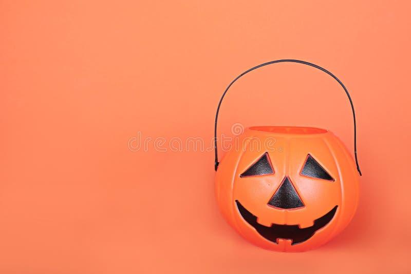 Ведро счастливого Джек-o-фонарика фокуса или обслуживания хеллоуина на оранжевой предпосылке Пластиковая тыква для того чтобы соб стоковое изображение rf