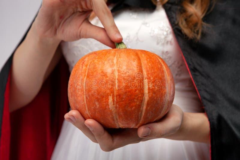 ведьма тыквы halloween Красивая молодая женщина в ведьмах шляпе и костюме держа тыкву Широкая партия хеллоуина стоковые изображения rf