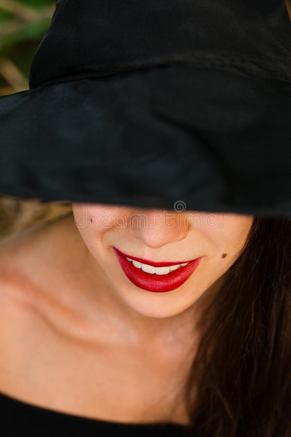 Ведьма хеллоуина в темной стороне конца-вверх леса с красными губами стоковые изображения rf