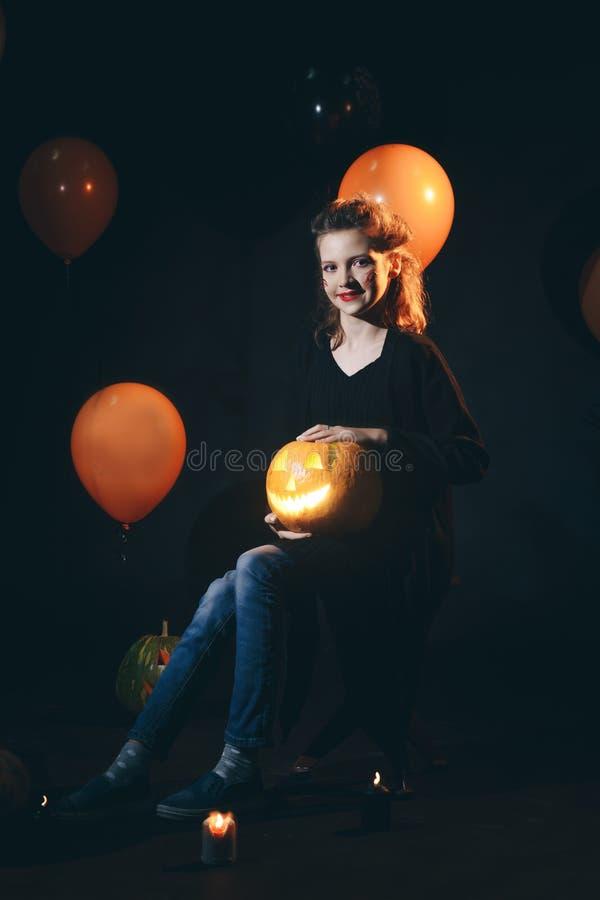 Ведьма хеллоуина с высекаенными тыквой и волшебством освещает в темными женщине леса красивыми удивленной детенышами в шляпе ведь стоковое изображение rf