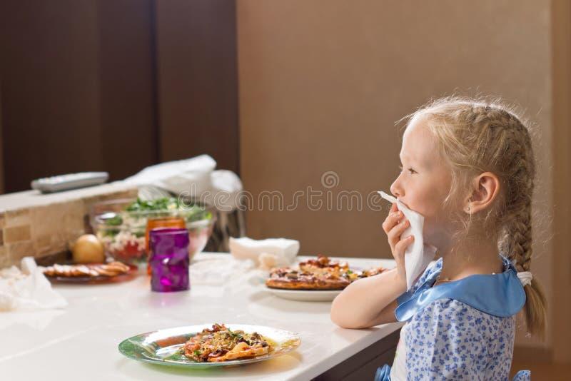 Вежливо маленькая девочка есть домодельную пиццу стоковые фотографии rf