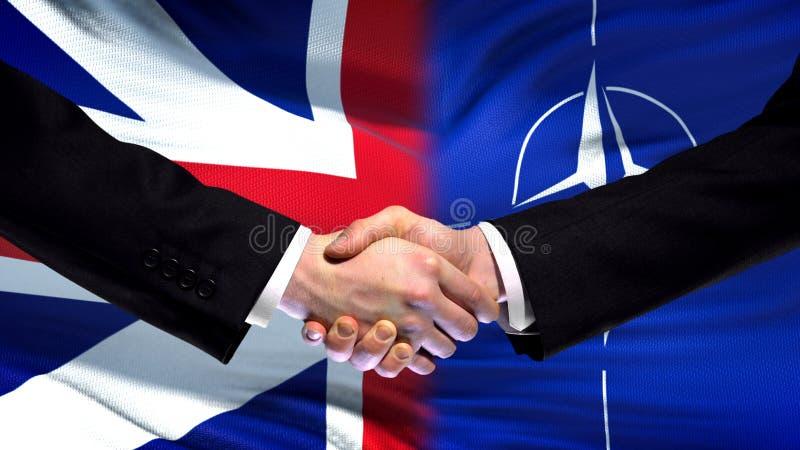 Великобритания и рукопожатие НАТО, международное приятельство, предпосылка флага стоковое фото rf