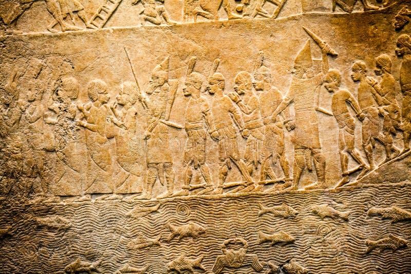ВЕЛИКОБРИТАНСКИЙ МУЗЕЙ - детали от ассирийской стены показывая египетские здания на заднем плане стоковое изображение