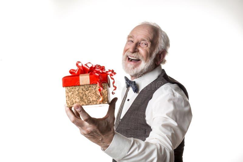 Великодушный пожилой человек давая настоящий момент стоковое фото