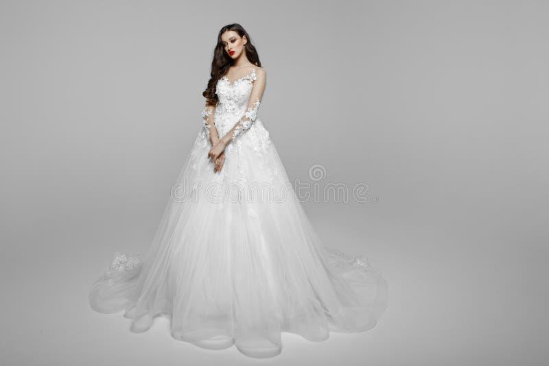 Великолепная девушка с вьющиеся волосы в платье свадьбы, держа руку совместно, стиль причесок, изолированный на белой предпосылке стоковые фотографии rf