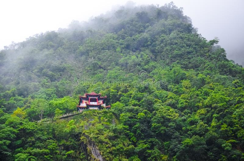 Великолепный китайский висок на крутом утесе окруженном погодой зеленого тропического леса туманной, туманом Тайваньский ландшафт стоковые фотографии rf