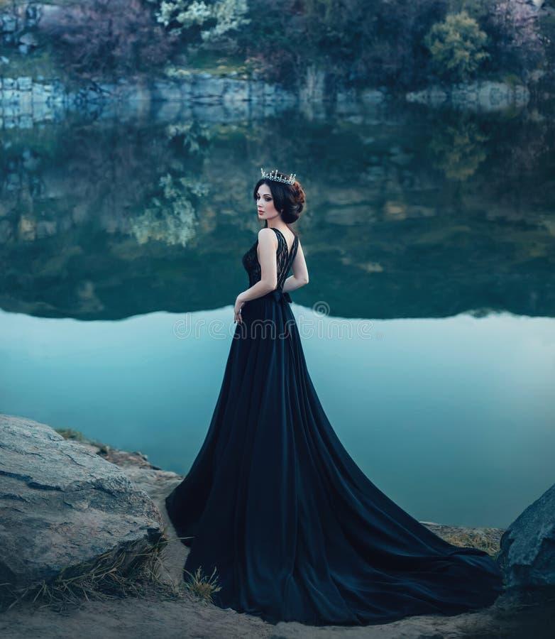 Величественная дама, темный ферзь, стойки на предпосылке реки и утесы, в длинном черном платье Девушка брюнет стоковое фото