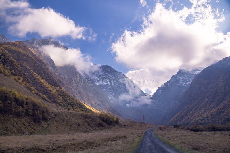 Величественный горный вид - скалистые пики с заплатами снега на горизонте с коричневатыми montains осени во фронте и водить дорог стоковые фото