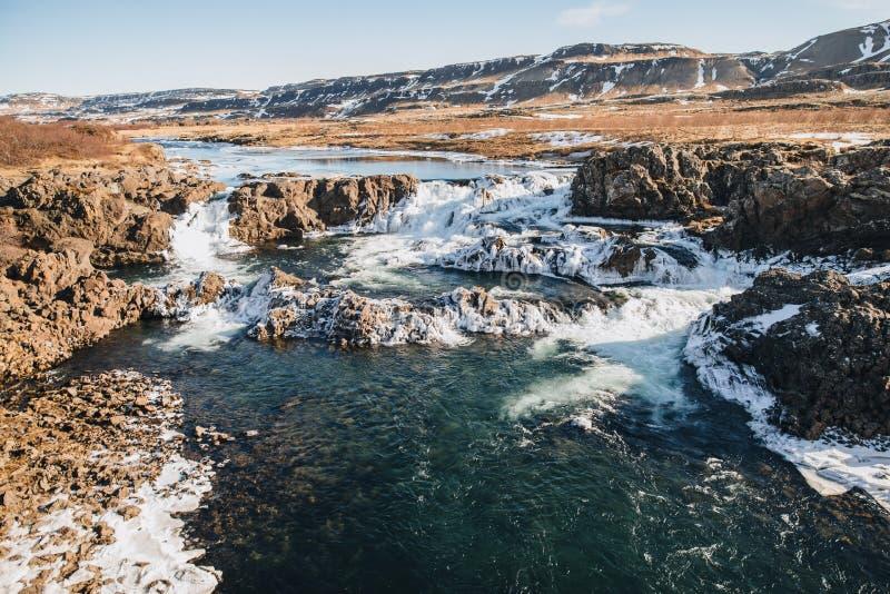 величественный исландский ландшафт с холмами и быстрым рекой на солнечном дне, стоковое фото rf