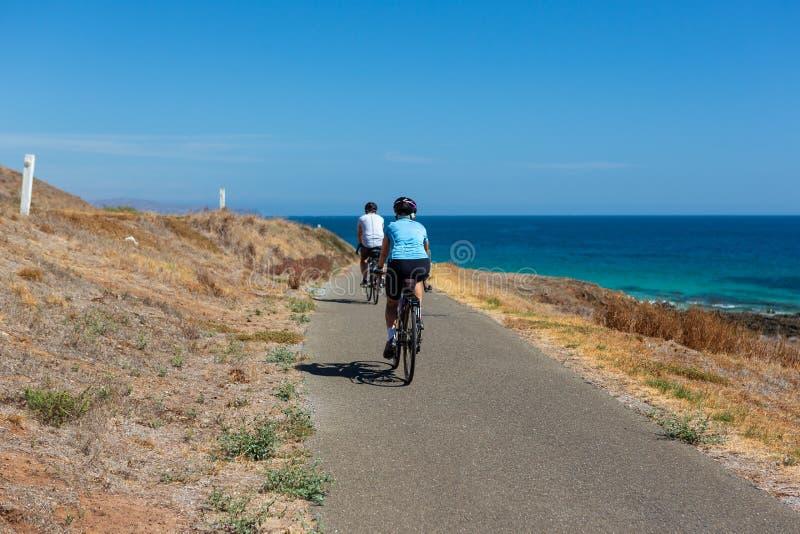 2 велосипедиста ехать вдоль следа велосипеда на красивом пляже Carrickalinga с Rolling Hills на заднем плане на Fleurieu p стоковое фото