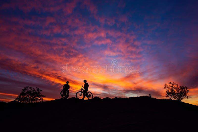 Велосипедисты горы silhouetted против красочного неба захода солнца в южном парке горы, Фениксе, Аризоне стоковые фотографии rf