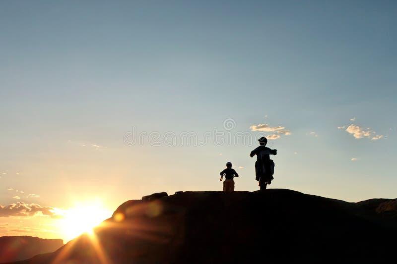 велосипедисты едут на автомобиле с захода солнца дороги стоковая фотография rf
