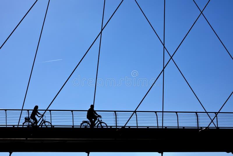 велосипедисты моста зреют силуэт стоковые изображения