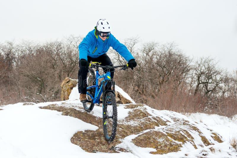 Велосипедист в голубом горном велосипеде катания на скалистом холме зимы покрытом с снегом Весьма спорт и концепция Enduro велоси стоковое фото