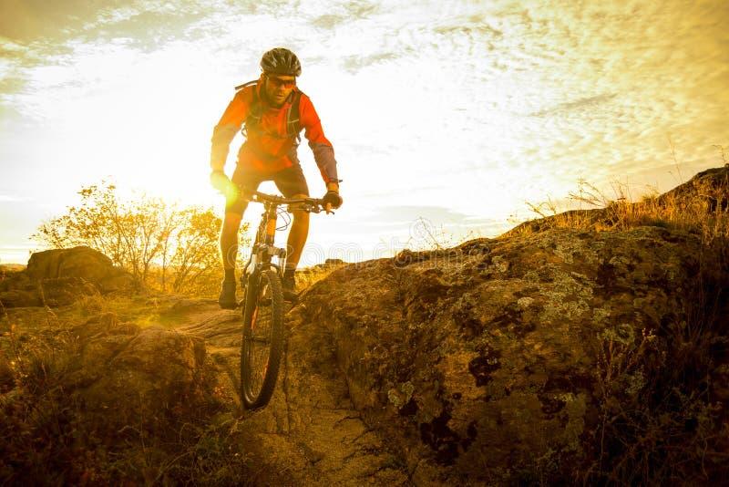 Велосипедист в красном цвете ехать велосипед на следе осени скалистом на заходе солнца Весьма спорт и концепция Enduro велосипед стоковые изображения rf