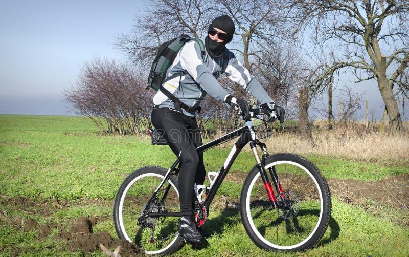 Велосипедист горы в поле стоковое изображение rf