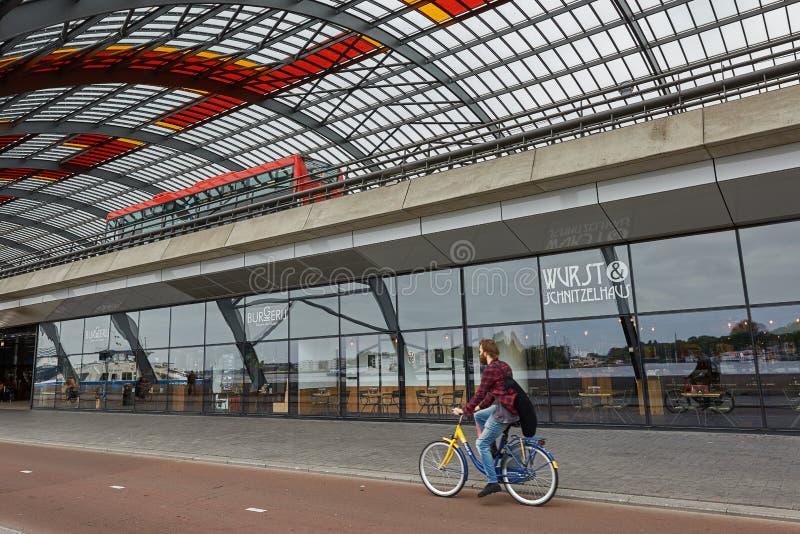 Велосипедист ехать велосипед вдоль вокзала в Амстердаме Нидерланд стоковые фото