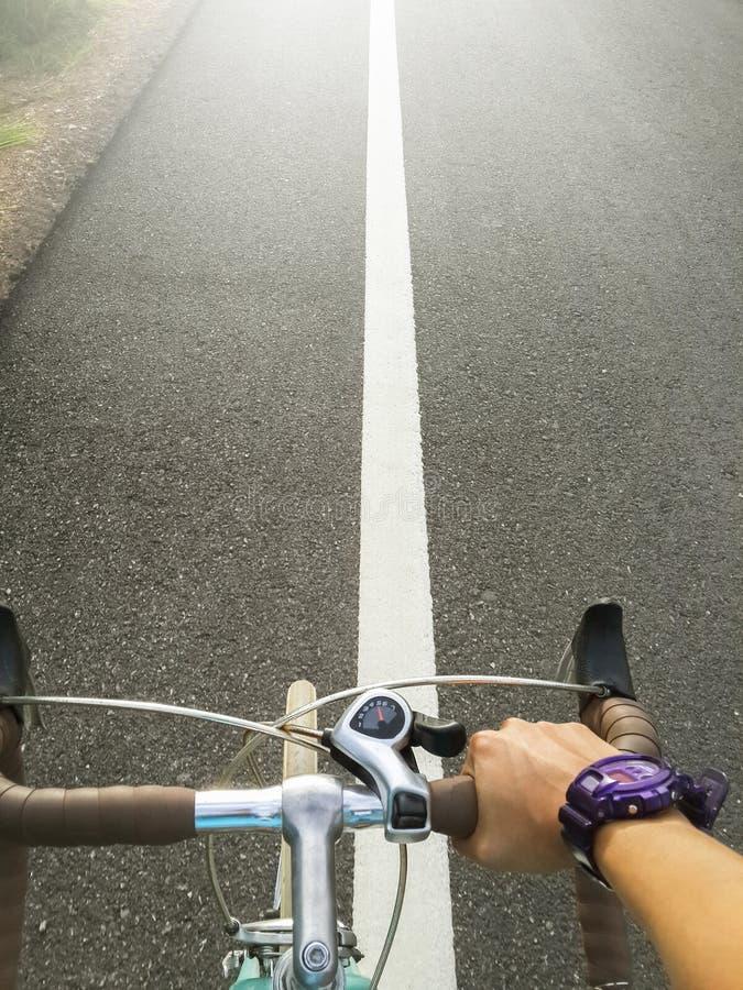 Велосипедист молодого человека велосипеда ручки на велосипеде дороги в предпосылке захода солнца стоковые изображения rf